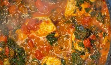 סיר דגים ברמונדי עם עגבניות, שום, זיתים וצמחי תבלין