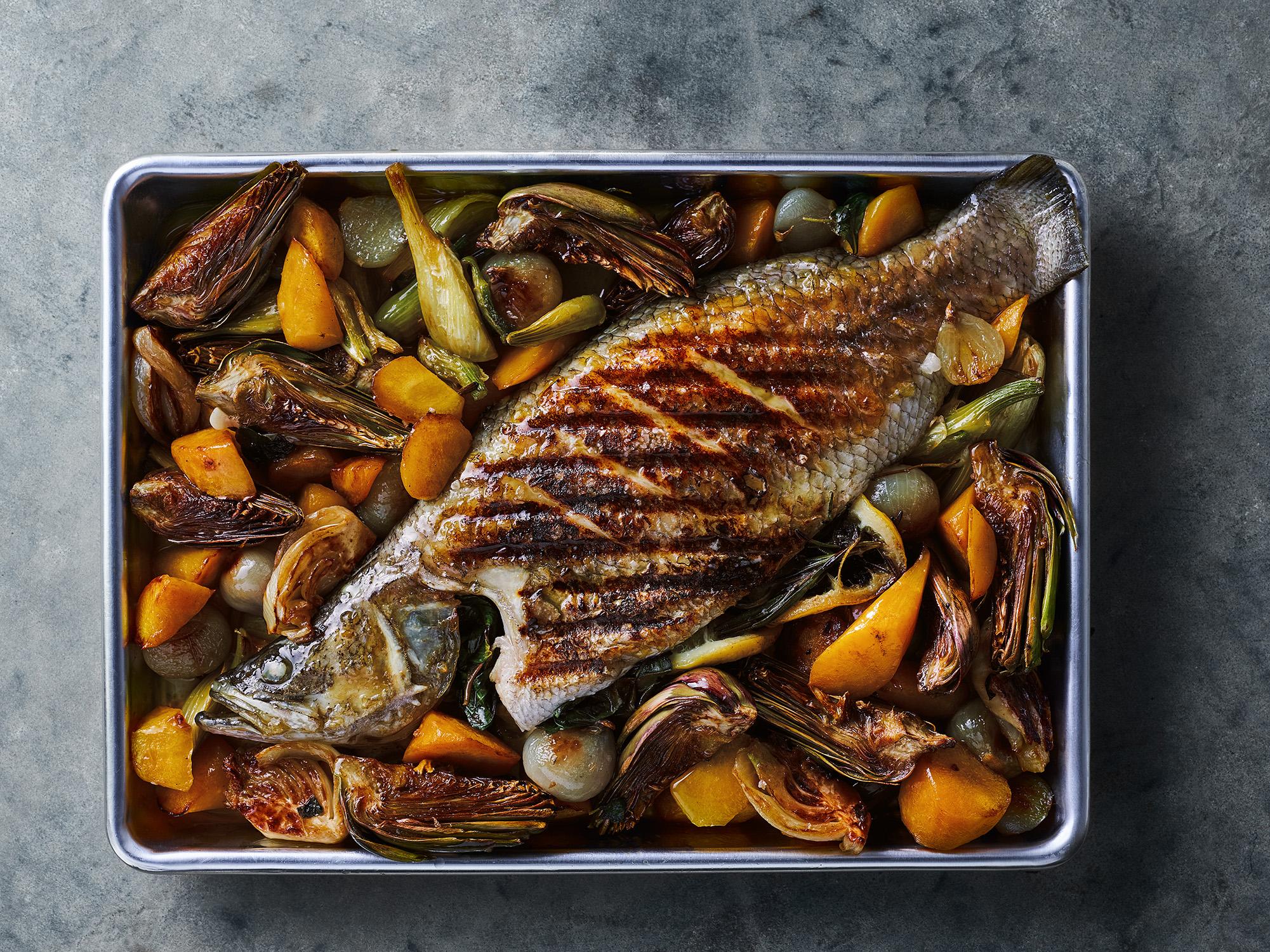 דג ברמונדי ישראלי שלם בתנור עם ארטישוק, גזרים ושומר ברוטב יין לבן
